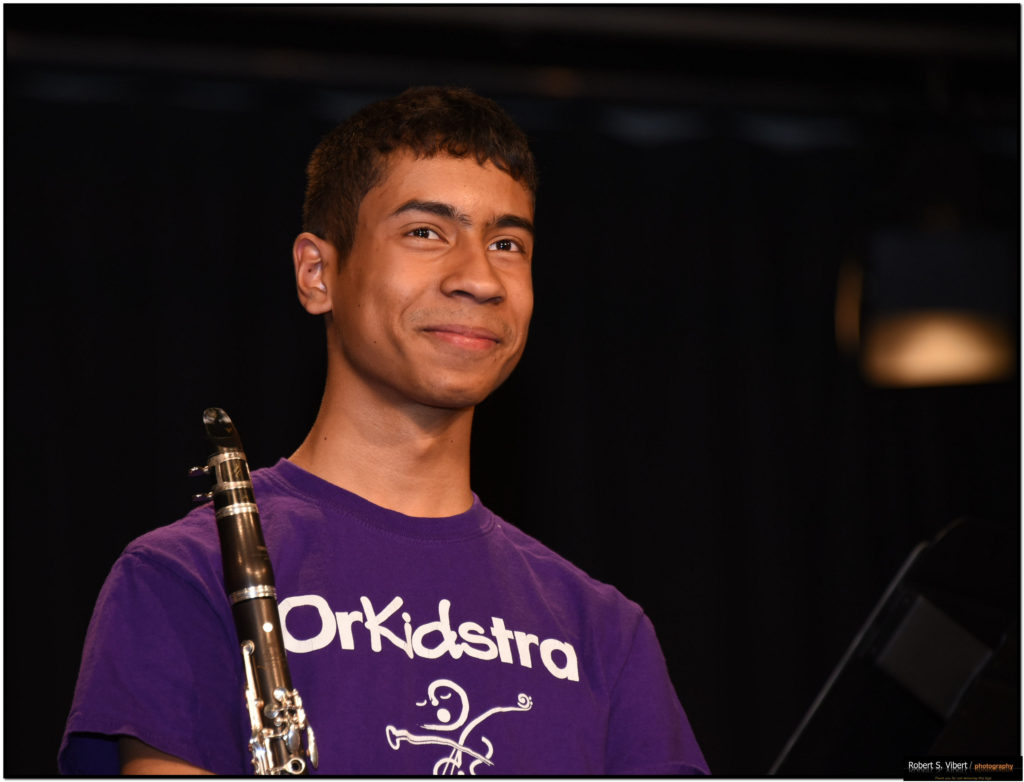 Photo of a young, male OrKidstra student named Peter holding a clarinet and smiling.