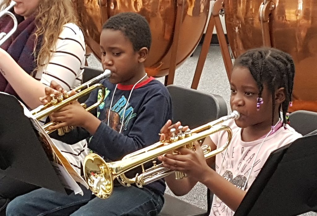 A young girl and boy playing trumpet