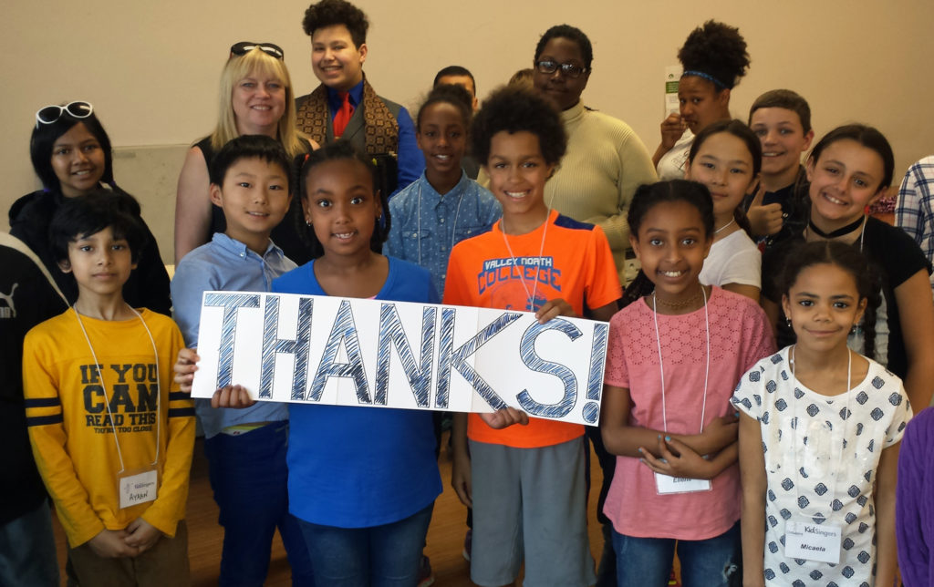 "A diverse group of children are smiling at the camera. They are holding a sign that says ""thanks!"""