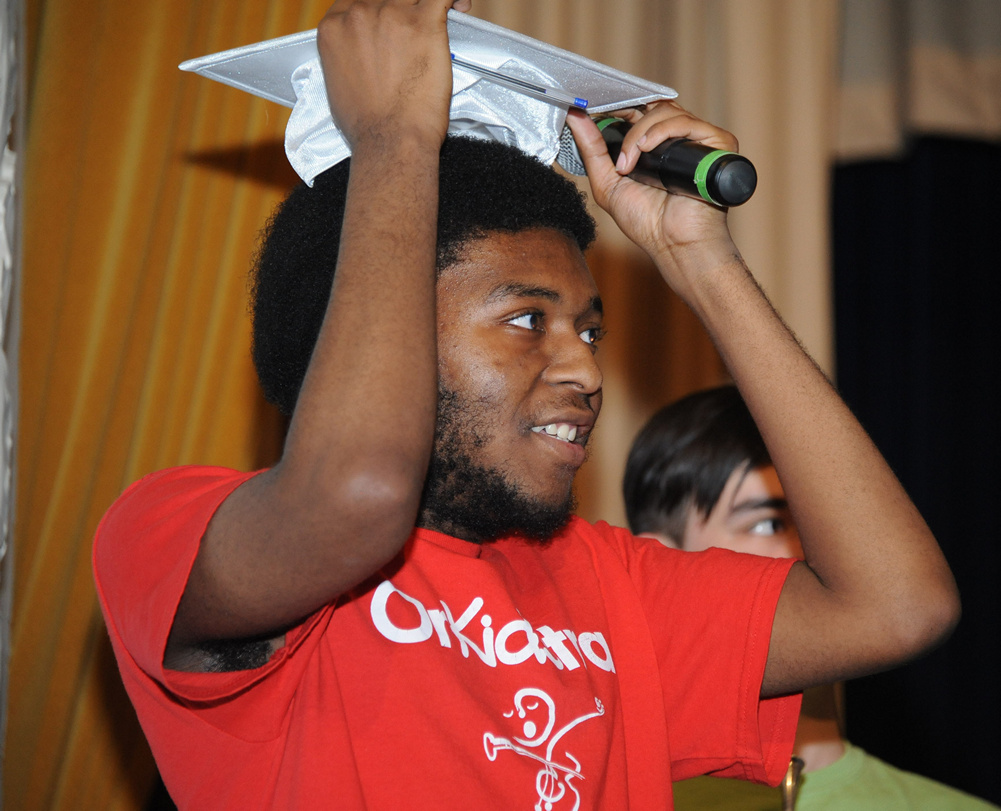 A young man holds a graduation cap. He is smiling.