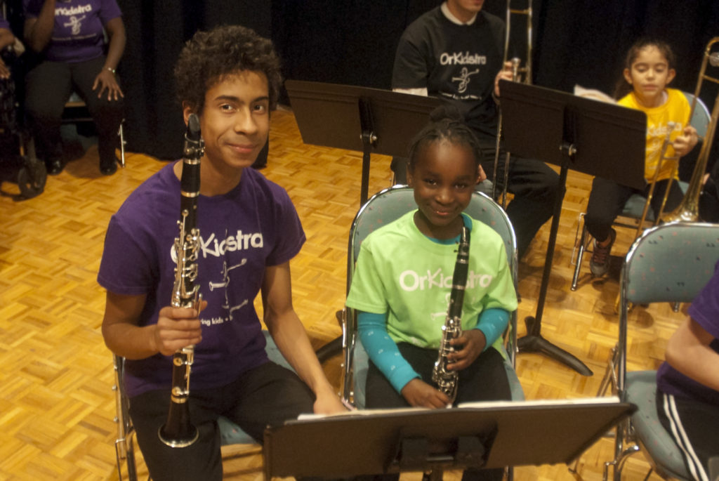 A photo of a teenage-boy and a younger girl smiling at the camera. They are both holding clarinets.