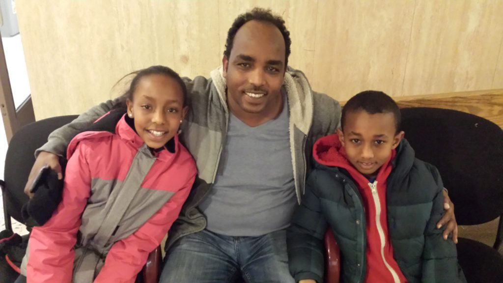 A photo of a family consisting of a father and two younger children smiling at the camera. The father is named Melake and two children are Shan and Sham.