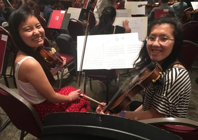 Two students smiling at the camera holding violins