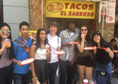 OrKidstra students and leaders stand in front of a taco stand in Mexico City