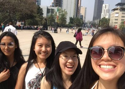 Four girls standing in a square in Mexico City and smiling