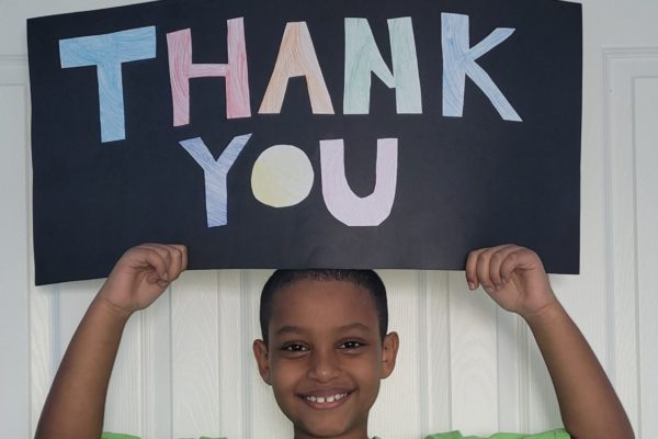A young boy holds a homemade thank you sign