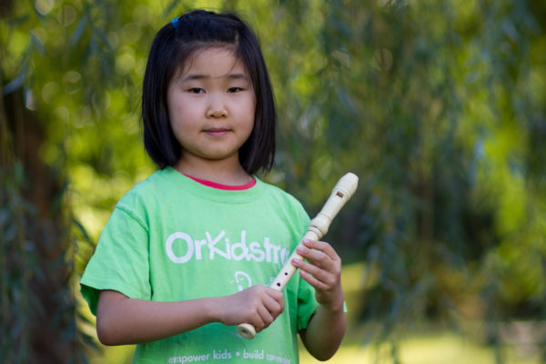 A photo of a child holding a recorder